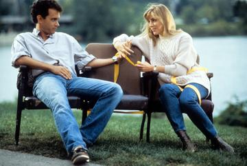 1986: Tom Hanks sits on a bench with a woman in a scene from the film 'Nothing In Common', 1986. (Photo by TriStar/Getty Images)