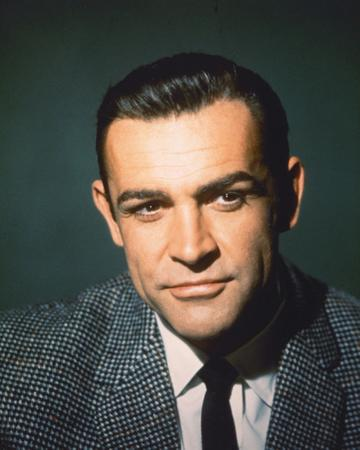 Sean Connery, British actor, wearing a grey tweed jacket, a white shirt and a black tie, in a studio portrait, against a dark green background, circa 1960. (Photo by Silver Screen Collection/Getty Images)