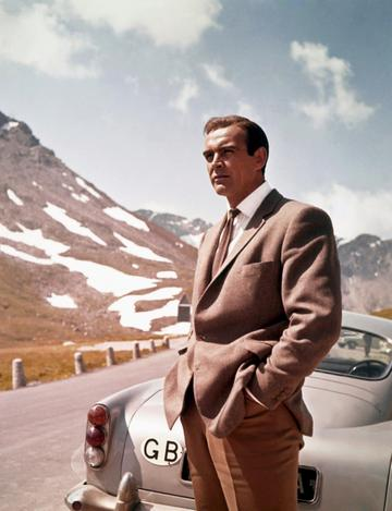 Actor Sean Connery poses as James Bond next to his Aston Martin DB5 in a scene from the United Artists film 'Goldfinger' in 1964 (Photo by Donaldson Collection/Michael Ochs Archives/Getty Images)